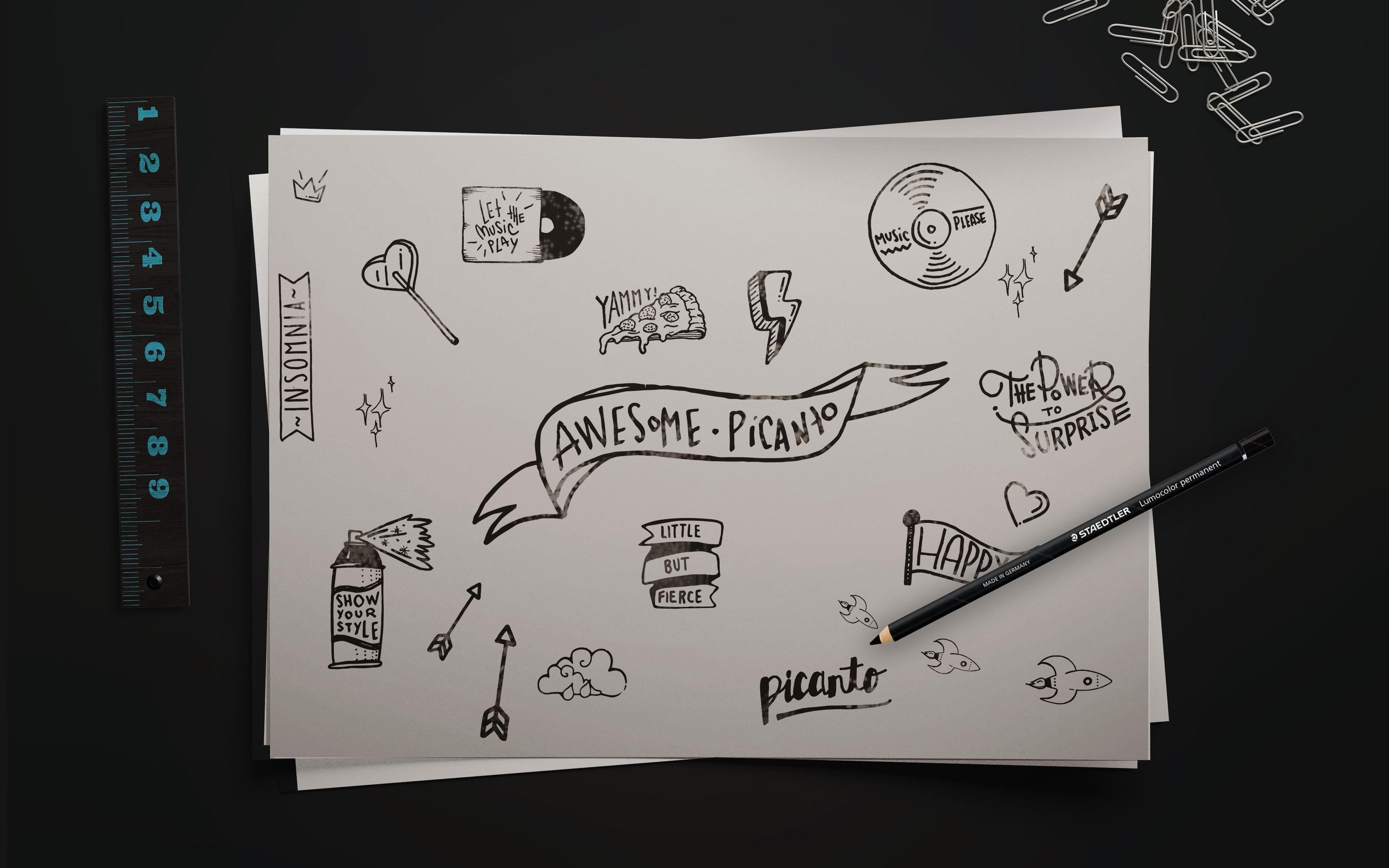Kia MyPicanto Desenho. Imagem de folha com desenhos feitos a lápis para o Kia MyPicanto. A imagem contém a folha em branco com os desenhos a preto, que servem para configurar o MyPicanto, um lápis pousado em cima da folha, uma régua e uns clips.